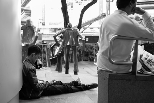 Guy texting outside Ion Orchard, Singapore