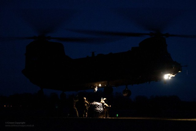 Soldiers Attaching Cargo to Chinook Helicopter at Night