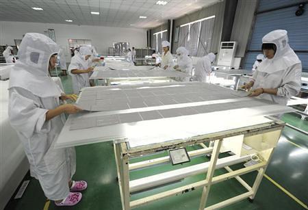资料图片:2012年7月26日,在合肥一家光伏企业的生产车间,工人们正在制作光伏组件。REUTERS/Stringer