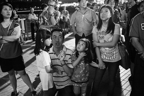A man teaching his 2 daughters about chinese culture and traditions pertaining to the god of fortune and the significance of the gold dust sprinkles.