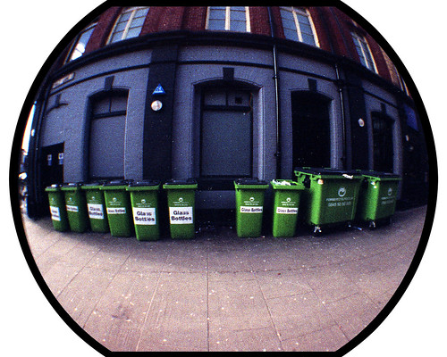 Ten green bottle bins standing against a wall by pho-Tony