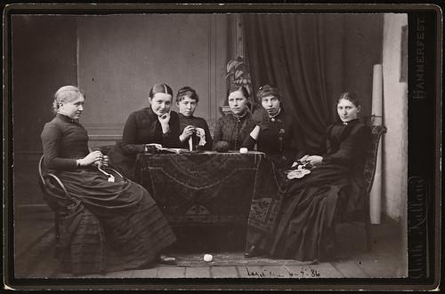 Portrett av gruppe uidentifiserte kvinner som hekler, strikker og leser, 1886