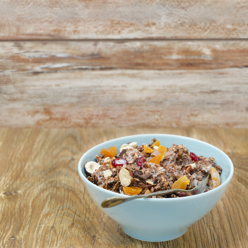 Chocolate granola with nuts and dried fruit and milk on a wooden table
