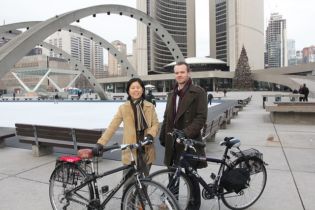 Woman and man each on their bikes with the Toronto City Hall in the background