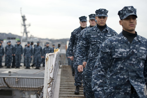 Sailors cross the brow during a hull swap ceremony between USS Cowpens and USS Antietam