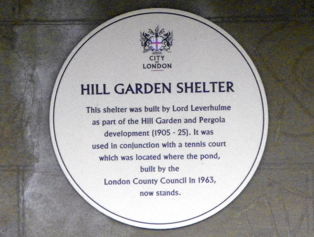 White plaque № 12137 - Hill Garden Shelter. This shelter was built by Lord Leverhulme as part of the Hill Garden and Pergola development (1905 - 25). It was used in conjunction with a tennis court which was located where the pond, built by the London County Council in 1963, now stands.