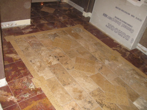 Travertine tile insert surrounded by red marble