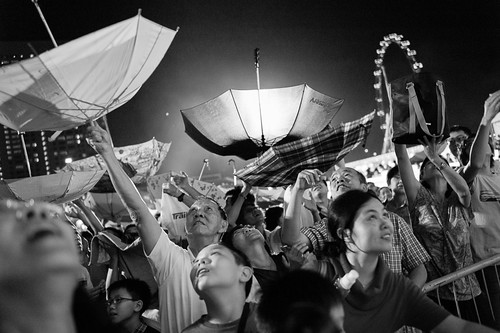 Believers in the god of fortune raised inverted umbrellas and looked skywards as they hope to catch a few of the gold dust signifying good fortune for the year.