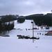 """Celkový pohled na středisko z """"náměstí"""". Na horizontu vlevo Medvědí, uprostřed lanovka, napravo Hřebenovka. Uprostřed fotky sjezdovka K Snowparku s kotvou. Uprostřed dole provázkový přibližovací vlek a příchod ke sjezdovkám."""