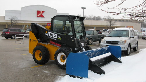 A small Caterpillar 4 wheel front end loader tractor equipped with a snowplow.  Des Plaines Illinois.  Monday, February 4th, 2013. by Eddie from Chicago