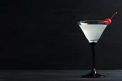 Cocktail in martini glass on the black wooden back…