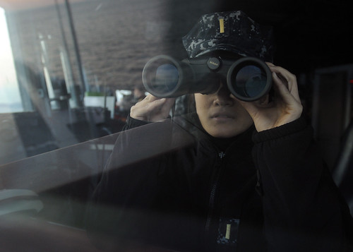 Ensign Maria Veloria uses a pair of binoculars to survey the surrounding waters of U.S.