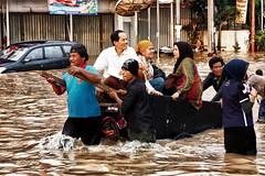 雅加達居民在洪水中涉水而過,2013年1月。(攝影:Ragil Tacilius)