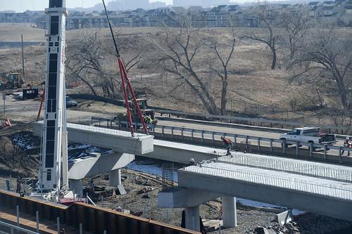 Photo of box girder being placed on Sand Creek commuter rail bridge
