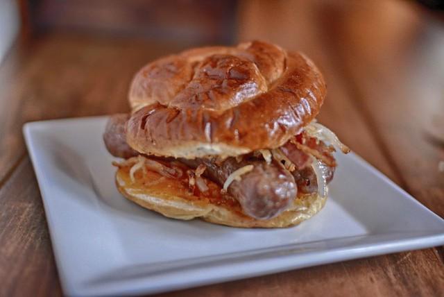 Pretzel bun bottom with melted cheddar, 2 Johnsonville brats, side by ...