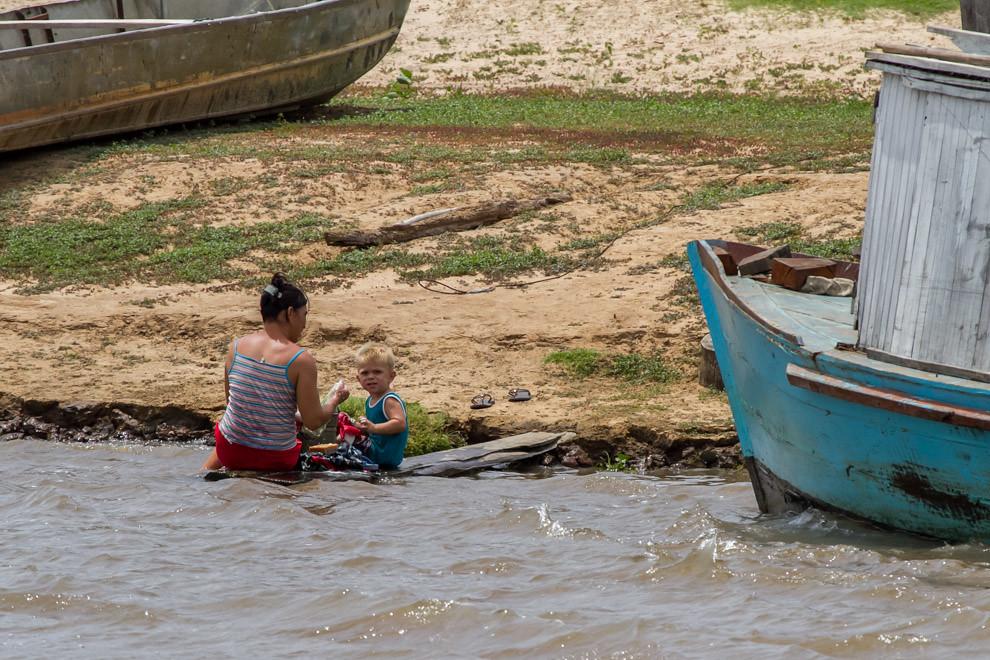 Esta mujer aprovecha las aguas del Río Paraguay para lavar ropas, en compañía de un pequeño que se encarga de darse un refrescante baño. (Tetsu Espósito)