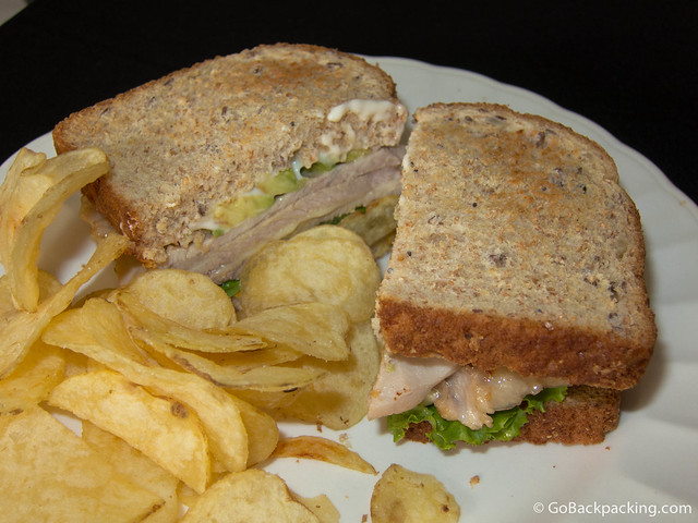 Ham and cheese sandwich with avocado, and a side of potato chips