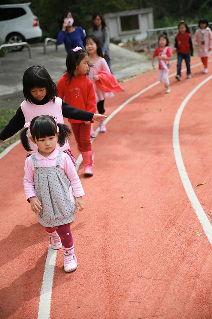 從操場回教室的路上,她莫名奇妙地變成了排頭,小朋友們排成一長條,順著跑道上的白線一路走回教室。
