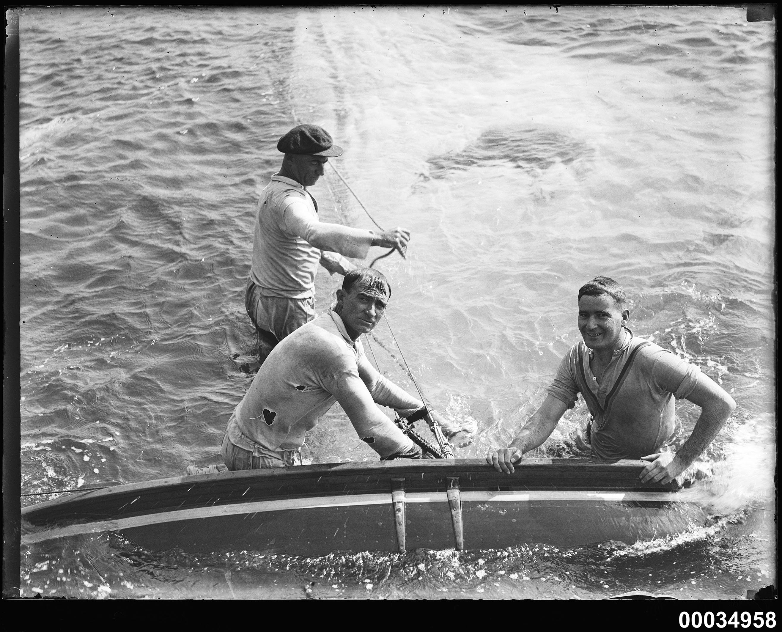 Image of three men in water with a capsized yacht