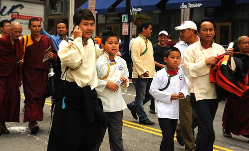 Tibetan men, boys, monks, wearing chubas, Tibetan style shirts, Buddhist maroon robes, walking in the street, talking on the cell, celebration of His Holiness the Great 14th Dalai Lama's birthday, Tibetans at Kalachakra, Washington D.C., USA by Wonderlane