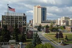 "Looking up ""I"" street, north, American flag, Park Strip, Nana Corporation, Marriott, parking garage, overcast day, Anchorage, Alaska, USA"