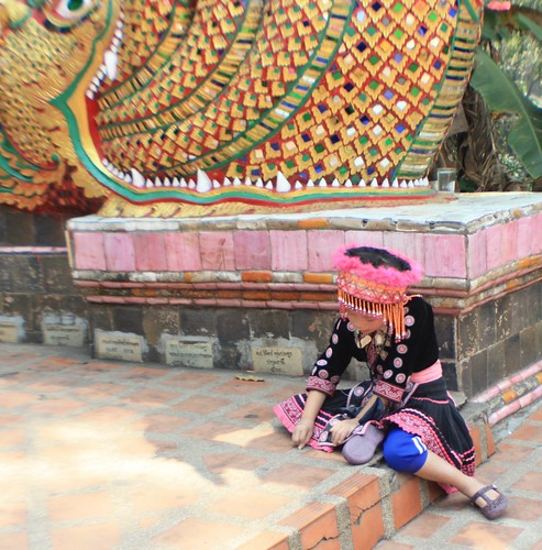 A Hmong girl playing at the bottom stairs leading up to Wat Phra That Doi Suthep