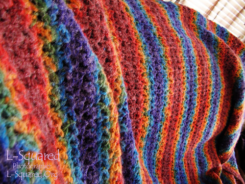 Close-up of the shell stitching on the colorful, striped blanket.