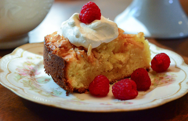 A slice of Almond Crunch Pound Cake with whipped cream and raspberries.