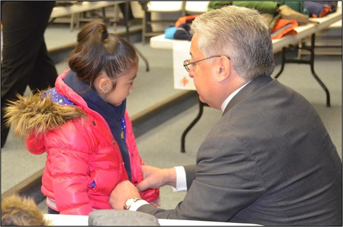 Photo of Greg Amparano, executive project director for Denver Transit Partners, helping a Swansea Elementary School student try on her new winter coat