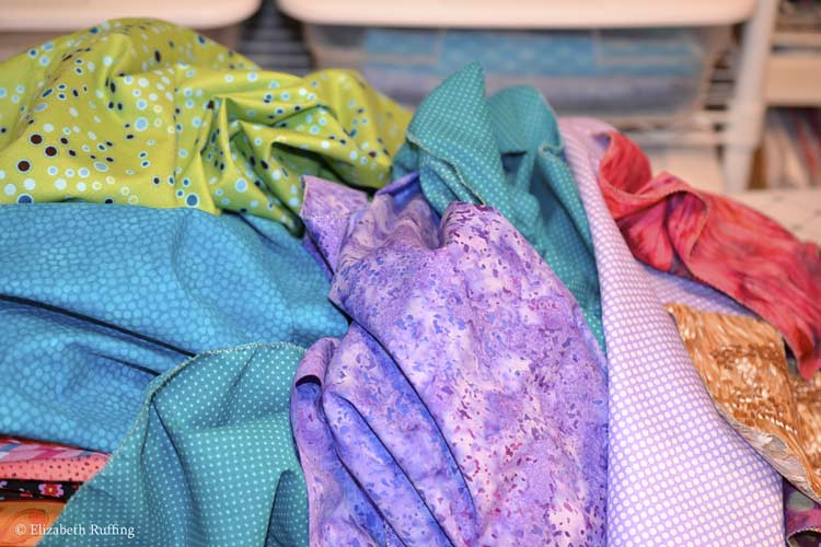 Pile of colorful fabrics, green, turquoise, purple, by Elizabeth Ruffing