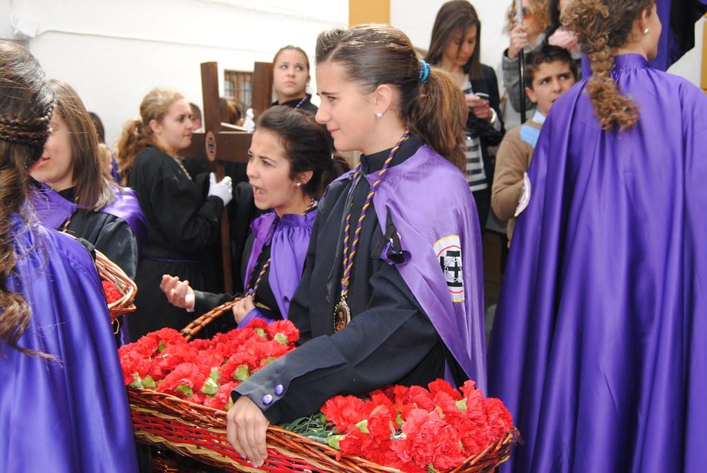 Las penitentes más jóvenes reparten claveles. FOTO: ÁNGEL MEDINA LAÍN