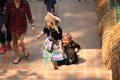 a Hmong boy chasing a Hmong girl up the stairs to Wat Phra That Doi Suthep