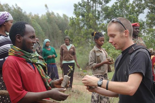 A Peace Corps Volunteer hands saplings to a community member.