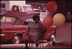 "Black Woman Selling Gas Filled ""Have A Happy Day"" Balloons On A Chicago South Side Street Corner At Sox Park Baseball Field, 06/1973"