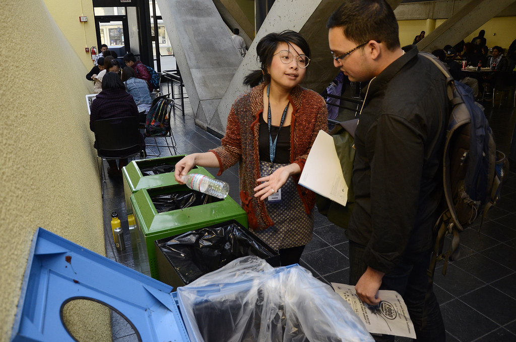 Sharon Daraphonhdeth (left), manager of student bin monitors and sustainable initiatives coordinator for Cesar Chavez Student Center, shows Taha Shaikh (right), bin monitor volunteer and business management major, how to sort out trash and put it into the proper bins on Tuesday, March 12, 2013. Photo by Virginia Tieman / Xpress