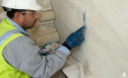 Workers repair the mortar joints between the marble on the façade.