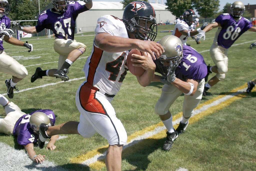 Ross Springman (15), Ryan Magnuson (86), and Erig Sarginson (87) pursue an Anderson University player during their season opener on September 1.  The Taylor University Trojans would lose the game 13-37.
