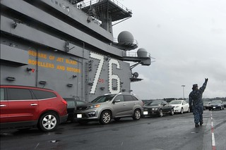 USS Ronald Reagan transports Sailor's cars during a port change.