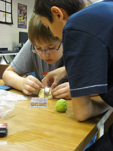 Two children concentrating on a squishy circuits creation on a table