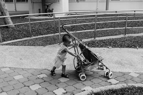 Kid pushing pram at old Tiong Bahru estate.