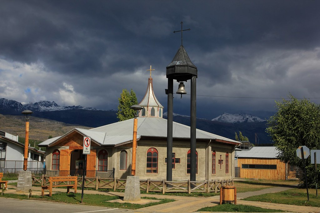 Dark clouds gather above the tiny church of Cochrane. Aysen, Patagonia, Chile.