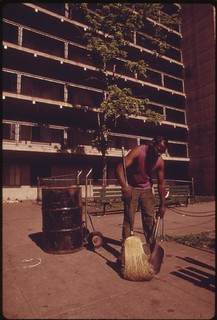 Sidewalk Trash Is Swept Up In Front Of One Of The Robert Taylor Highrise Low Income Apartment Projects Inhabited By Blacks On Chicago's South Side, 06/1973