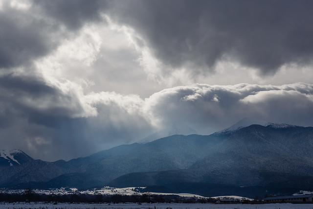 Gap in clouds of a snow storm over mountains