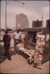 Black Man Operating A Newsstand In Chicago At 22nd And South State Street On The South Side, 07/1973