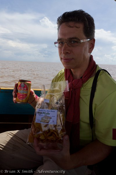 Rick Green drinking an Angkor on the Tonle Sap.