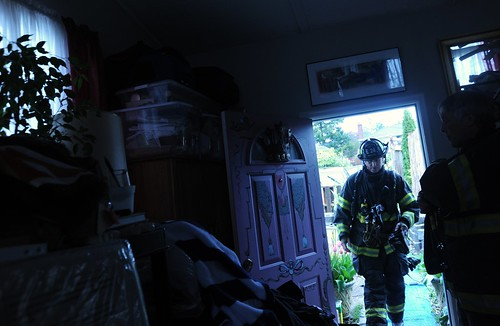 Firemen arrive to check out the source of the burning smell, pile of clean clothes taken from the moldy closet due to the leaking roof, substandard housing, Broadview Duplex, Seattle, Washington, USA by Wonderlane