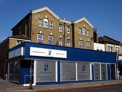 Part of a terrace of buildings, viewed on a sunny day with a deep blue sky.  On the ground floor is a shop frontage spanning three normal-sized shopfronts, painted in dark blue with large windows that appear silver-grey.  The older, brick-built part of the building rises above and behind, with two peaked gables.