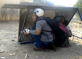 Two journalists and two children shelter from stone throwing militia