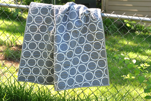 Quilt with Circular Pattern Hanging Over Chainlink Fence