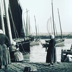 women making wool socks awaiting fisherman on the quay...